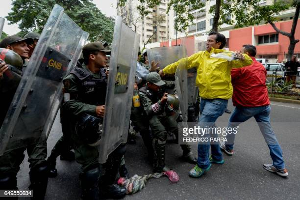 TOPSHOT Venezuela's National Guard personnel prevent Venezuelan opposition deputy Carlos Paparoni of the 'Primero Justicia' party from protesting in...