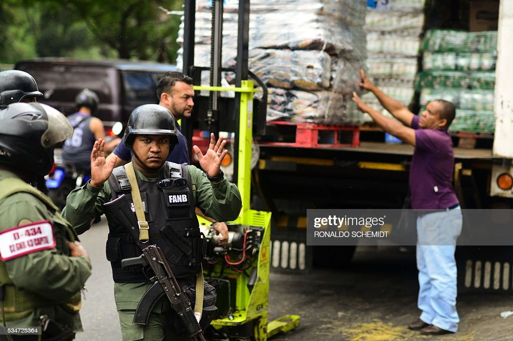 Venezuela´s National police members stand guard outside a supermarket while people line up to buy basic food and household items in the poor neighborhood of Lidice, in Caracas, Venezuela on May 27, 2016. President Nicolas Maduro announced a process of 'review and correction,' including combating corrupt practices, following his party's crushing defeat in parliamentary elections in December. / AFP / RONALDO