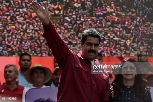 Venezuela's President Nicolas Maduro greets the crowd with his wife Cilia Flores during a rally supporting Maduro and opposing US President Donald...