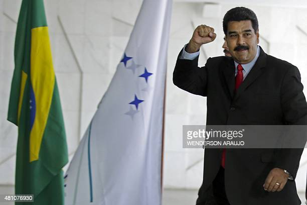 Venezuela's President Nicolas Maduro raises his fist as he arrives to the MERCOSUR Summit of Heads of State and Associated States at Itamaraty Palace...