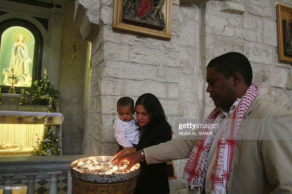 Venezuela's representative to the Palestinian Authority Luis Hernandez (R) and his family light candles during Sunday mass at the Church of the Nativity in the West Bank Town of Bethlehem on December 16, 2012. A prayer was held for Venezuela's President Hugo Chavez who is recovering from his fourth cancer operation since being diagnosed last year.