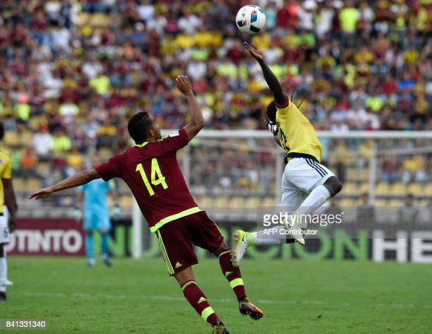 Venezuela's Yangel Herrera and Colombia's Yimmi Chara vie for the ball during their 2018 World Cup qualifier football match in San Cristobal...