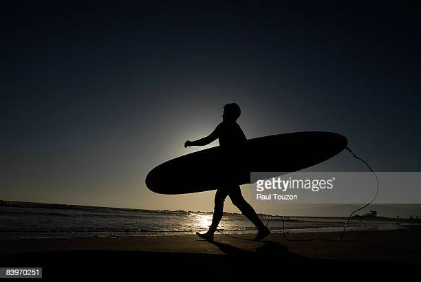 A surfer walks toward the ocean with his board at sunset.