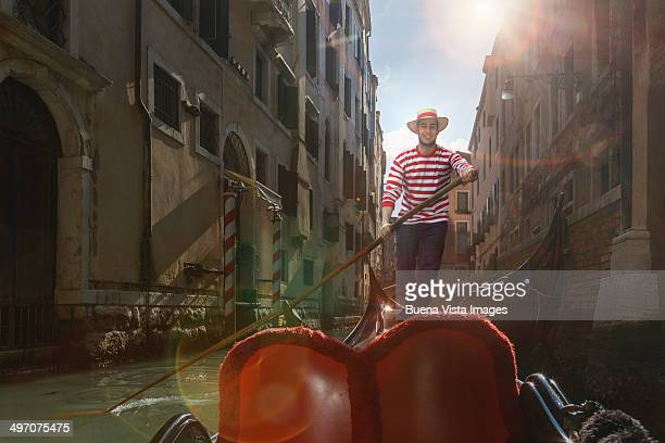 Venice, gondolier on gondola in a channel