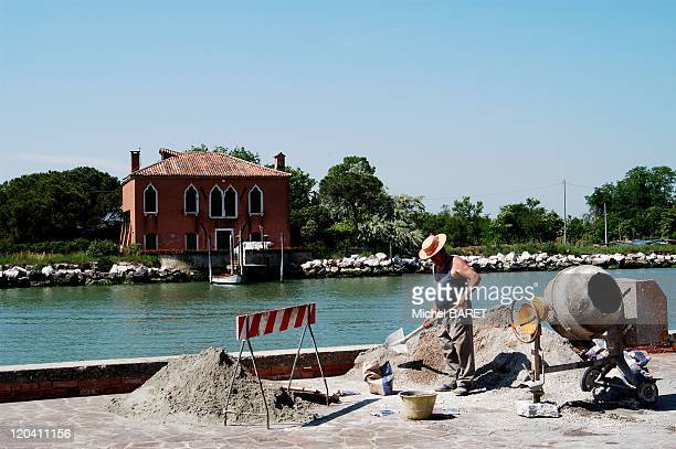 Venice Italy On Mazzorbho Island a worker is preparing concrete with a cement mixer on a small site under construction facing a house standing on the...