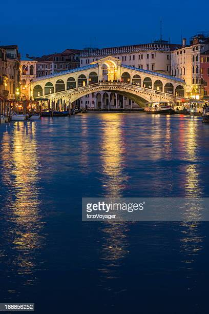 Venice Rialto Bridge illuminated at dusk over Grand Canal Italy
