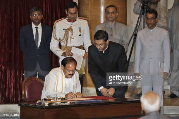 Venkaiah Naidu signs the official book after being sworn in as India's new vice president as outgoing Vice President Hamid Ansari watches at the...