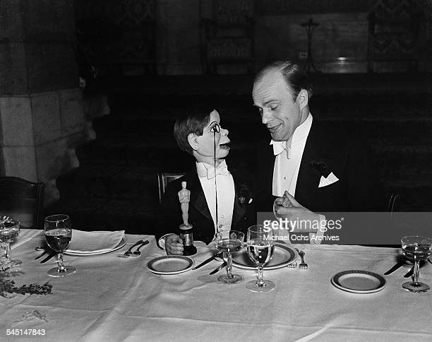 Ventriloquist Edgar Bergen and Charlie McCarthy sit at a table with a mini wooden Oscar statue during the 10th Academy Awards in Los Angeles...