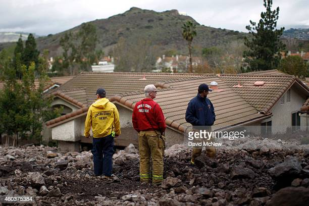 Ventura County firefighters stand on a pile of rocks and mud after debris flows smashed into homes as a powerful storm that has been lashing northern...