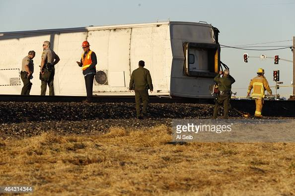 Ventura County Sheriff's Deputies and first responders inspects a overturned Metrolink train car after colliding with a vehicle on the tracks...