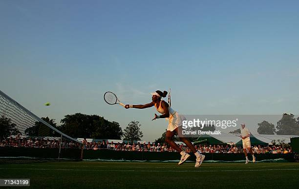 Venus Williams of the United States hits a volley while playing with doubles partner Bob Bryan of the United States against Jeff Coetzee of South...