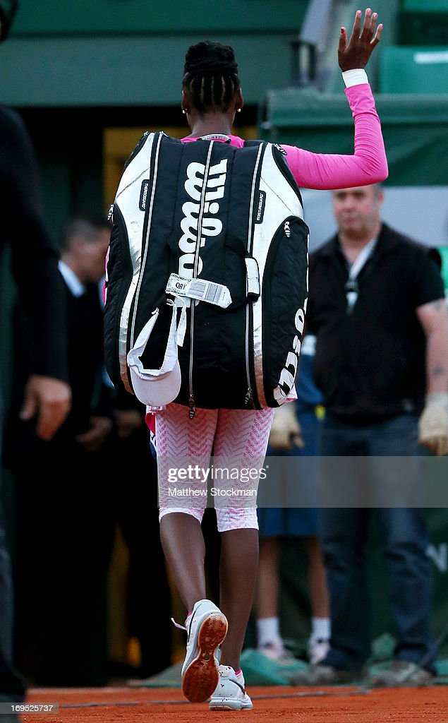 Venus Williams of the United States of America waves as she leaves the court after defeat in her women's singles match against Urszula Radwanska of Poland on day one of the French Open at Roland Garros on May 26, 2013 in Paris, France.