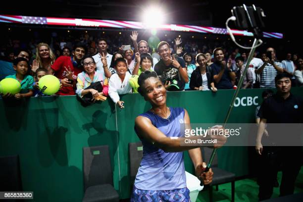 Venus Williams of the United States takes a selfie with fans as she celebrates victory in her singles match against Jelena Ostapenko of Latvia during...