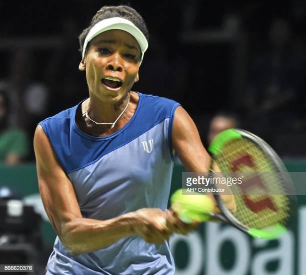 Venus Williams of the US hits a return against Garbine Muguruza of Spain during the WTA Finals tennis tournament in Singapore on October 26 2017 /...