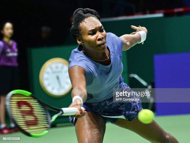 Venus Williams of the US hits a return against Karolina Pliskova of the Czech Republic during the WTA Finals tennis tournament in Singapore on...