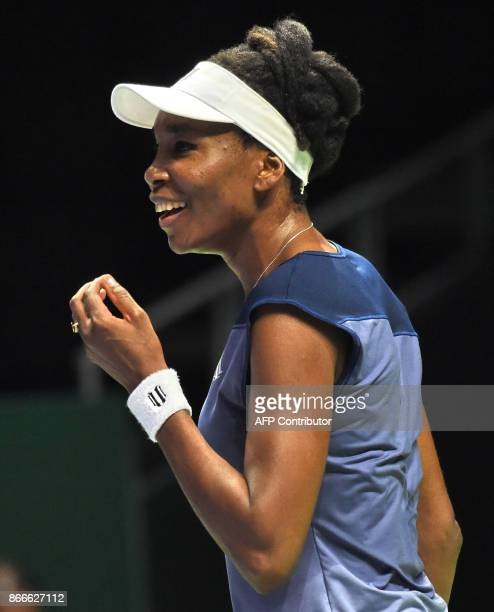 Venus Williams of the US reacts after a shot against Garbine Muguruza of Spain during the WTA Finals tennis tournament in Singapore on October 26...
