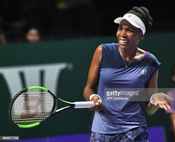 Venus Williams of the US reacts to a shot in a match against Garbine Muguruza of Spain during the WTA Finals tennis tournament in Singapore on...