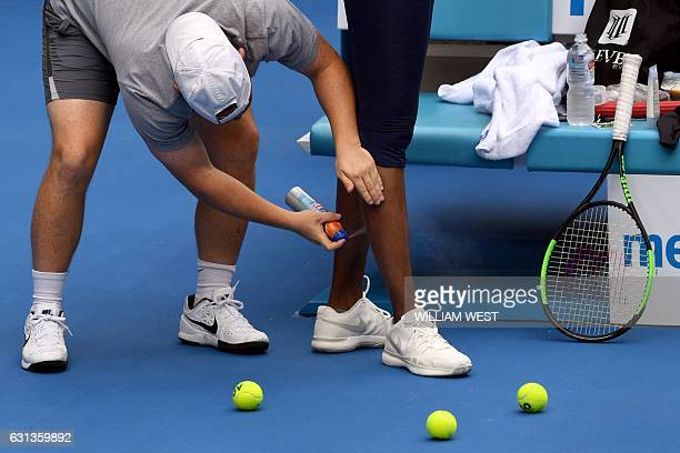 Venus Williams of the US receives a spray to her leg before a tennis training session in Melbourne on January 10 2017 Top players from around the...