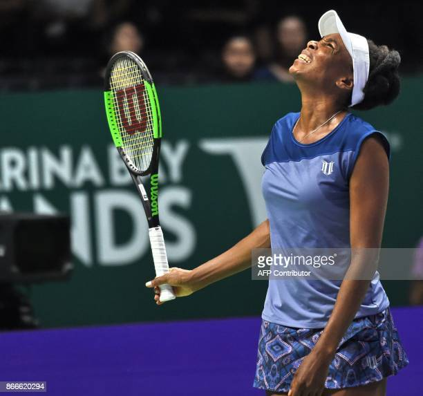 Venus Williams of the US sreacts to a point against Garbine Muguruza of Spain during the WTA Finals tennis tournament in Singapore on October 26 2017...