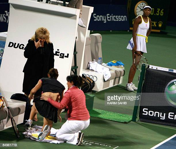 Venus Williams of the US watches as France's Virginie Razzano receives attention from a physiotherapist for lower back pain during their WTA Dubai...