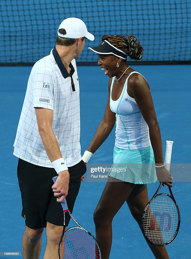 Venus Williams of the USA laughs with John Isner in their mixed doubles match against Chanelle Scheepers and Kevin Anderson of South Africa during day two of the Hopman Cup at Perth Arena on December 30, 2012 in Perth, Australia.