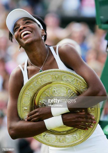 Venus Williams of USA hugs the trophy following her victory during the Women's Singles final match against Marion Bartoli of France during day twelve...