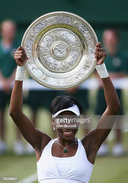 Venus Williams of USA lifts the trophy following her victory during the Women's Singles final match against Marion Bartoli of France during day...