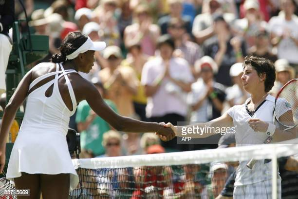 US Venus Williams shakes hands after winning against Spain's Carla Suarez Navarro during their match on Day 6 at the 2009 Wimbledon tennis...