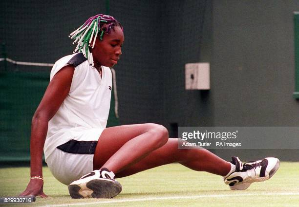 Venus Williams skids on the slippery surface of Wimbledon's No 1 Court this afternoon during her first round match against Poland's Magdelena...