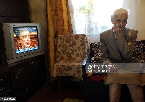 Vera Yunets a ProRussian supporter aged 83 wearing military decorations watches a TV broadcast of the inauguration of Ukrainian President Petro...