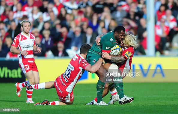Vereniki Goneva of Leicester Tigers is tackled by Mark Atkinson and Richard Hibbard of Gloucester during the Aviva Premiership match between...