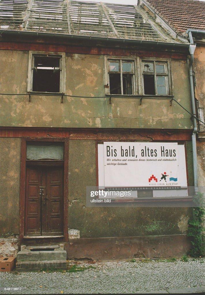 Verfallenes Haus Mit Kaputten Fensterscheiben Und Abgedecktem Dach Schild  Der U0027Stadterneuerung Brandenburgu0027 An Der