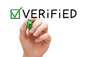 Hand putting check mark on Verified with green marker isolated on white. 'n