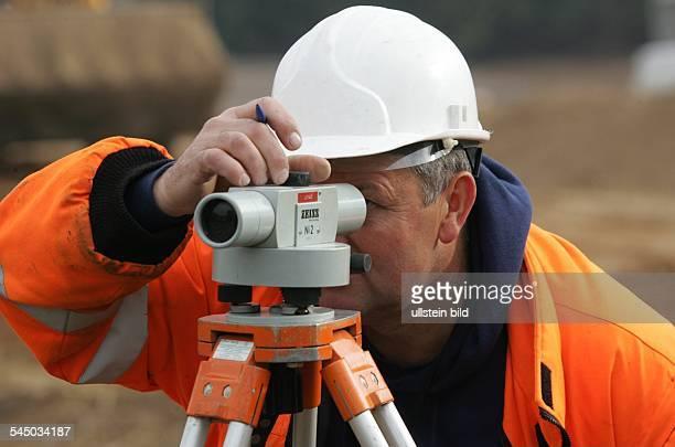 Vermessung Bauingenieur mit Nivelliergerät von Zeiss Messgeraet mit dem Höhenhorizonte hergestellt und Hoehenunterschiede gemessen werden um...