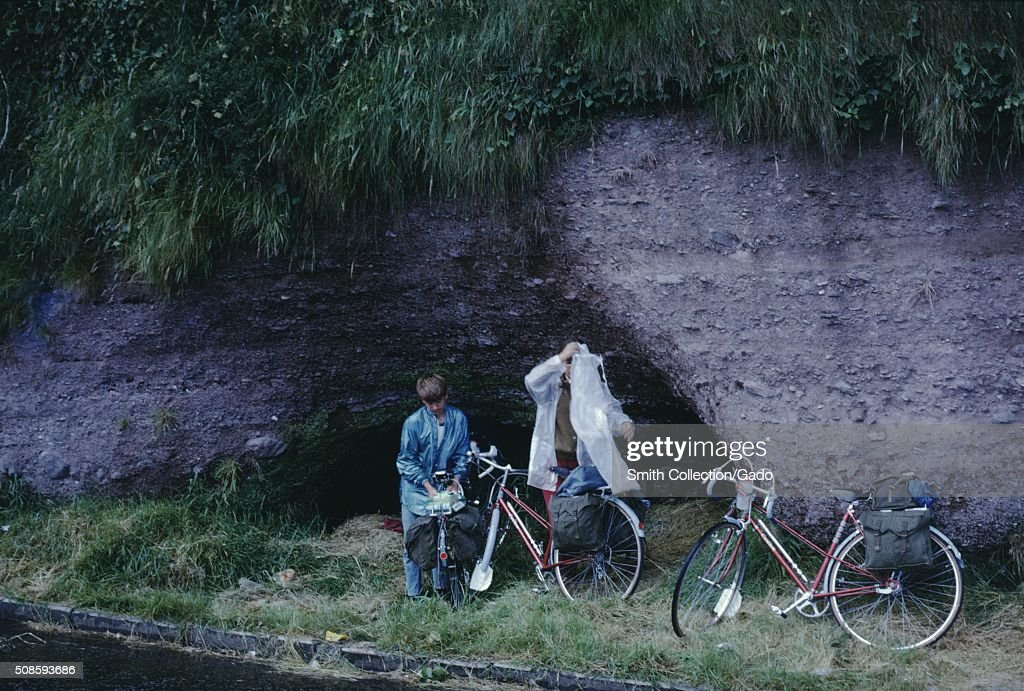Vernacular snapshot photograph of kids on bikes putting on rain slickers, 1966. (Photo by Smith Collection/Gado/Getty Images).