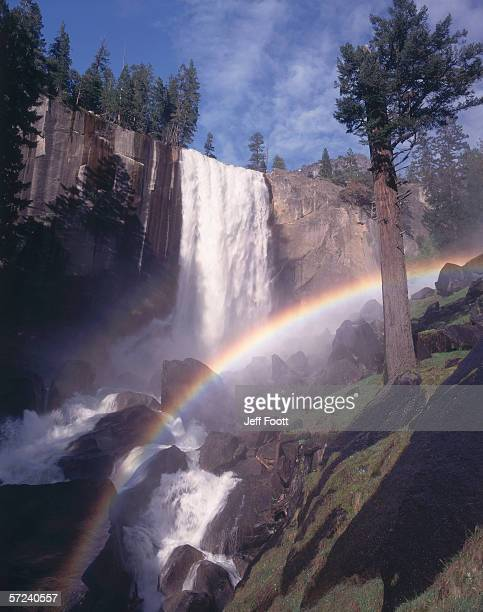 Vernal falls cascades into a lush valley. A rainbow arches over a waterfall as it cascades into rocks in the valley below. Yosemite National Park, California