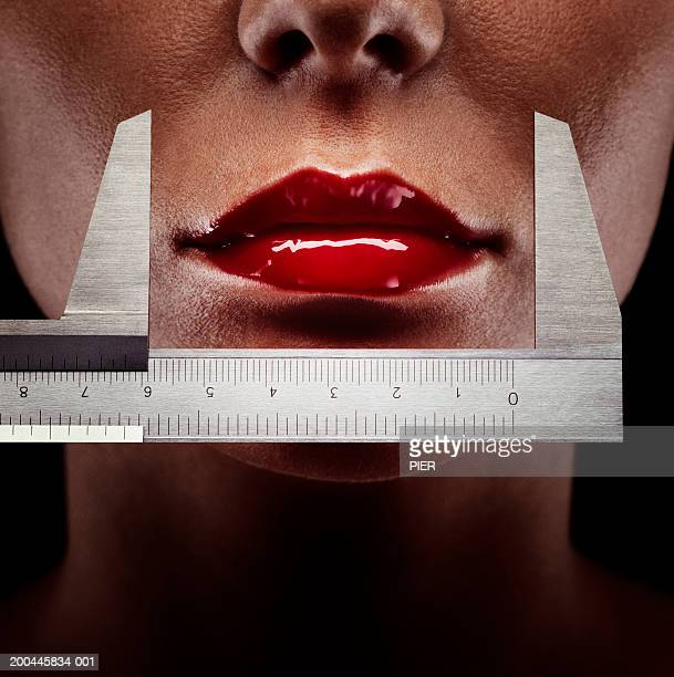 Vernier calliper measuring woman's lips, close-up