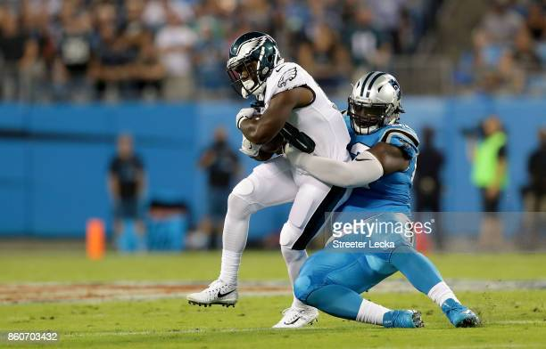 Vernon Butler of the Carolina Panthers tackles Kenjon Barner of the Philadelphia Eagles in the first quarter during their game at Bank of America...