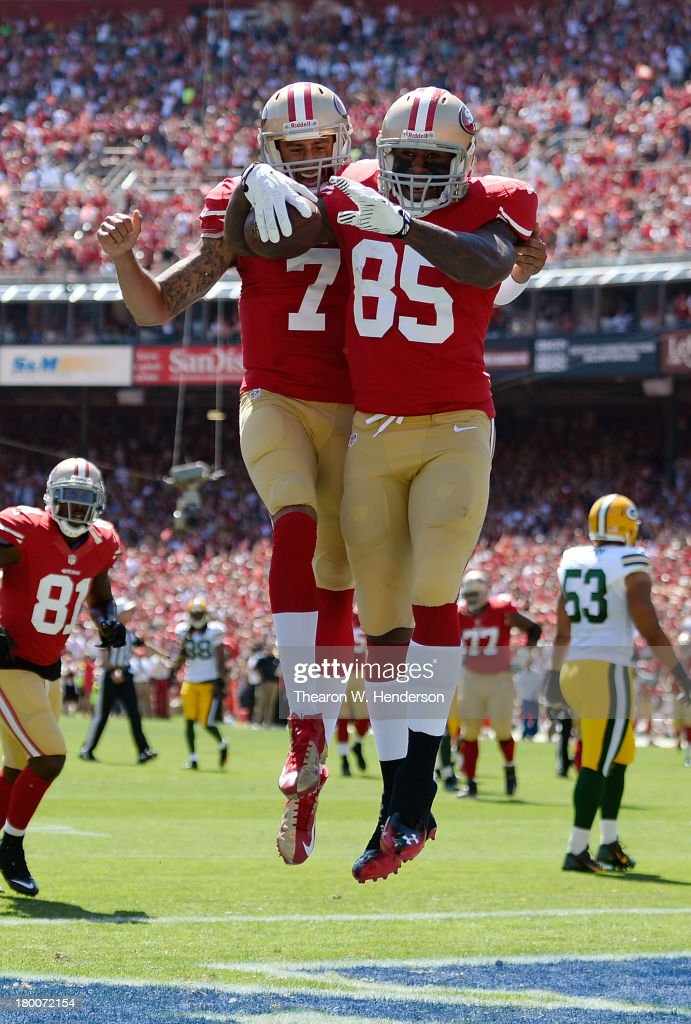 Vernon Davis #85 and Colin Kaepernick #7 of the San Francisco 49ers celebrate after Davis caught a twenty two yard touchddown pass in the first quarter against the Green Bay Packers at Candlestick Park on September 8, 2013 in San Francisco, California.