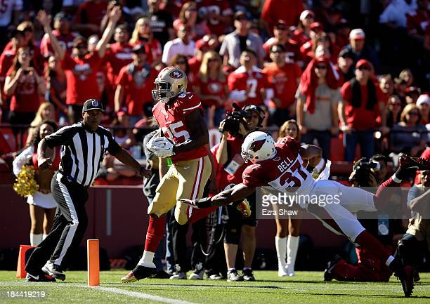 Vernon Davis of the San Francisco 49ers gets past a diving Yeremiah Bell of the Arizona Cardinals to score a touchdown at Candlestick Park on October...