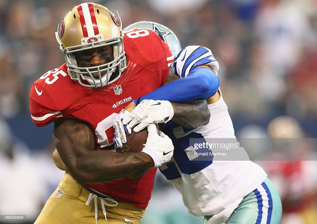 Vernon Davis of the San Francisco 49ers runs the ball against Sterling Moore of the Dallas Cowboys at ATT Stadium on September 7 2014 in Arlington...
