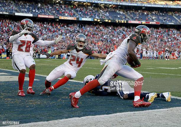 Vernon Hargreaves III and Brent Grimes of the Tampa Bay Buccaneers celebrate an interception by Keith Tandy as Dontrelle Inman of the San Diego...