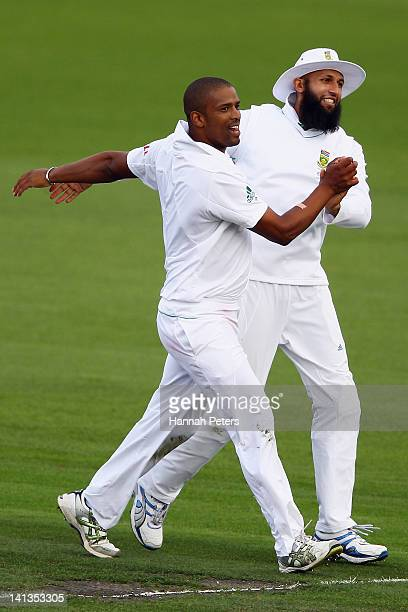 Vernon Philander celebrates with Hashim Amla of South Africa after claiming the wicket of Ross Taylor of New Zealand during day one of the First Test...