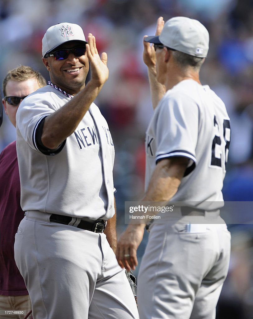 Vernon Wells #12 and Joe Girardi #28 of the New York Yankees celebrate a win of the game against the Minnesota Twins on July 4, 2013 at Target Field in Minneapolis, Minnesota. The Yankees defeated the Twins 9-5.