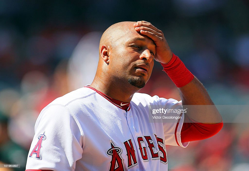 Vernon Wells of the Los Angeles Angels of Anaheim wipes his forehead after reaching first base on an infield single during a break in action in the...