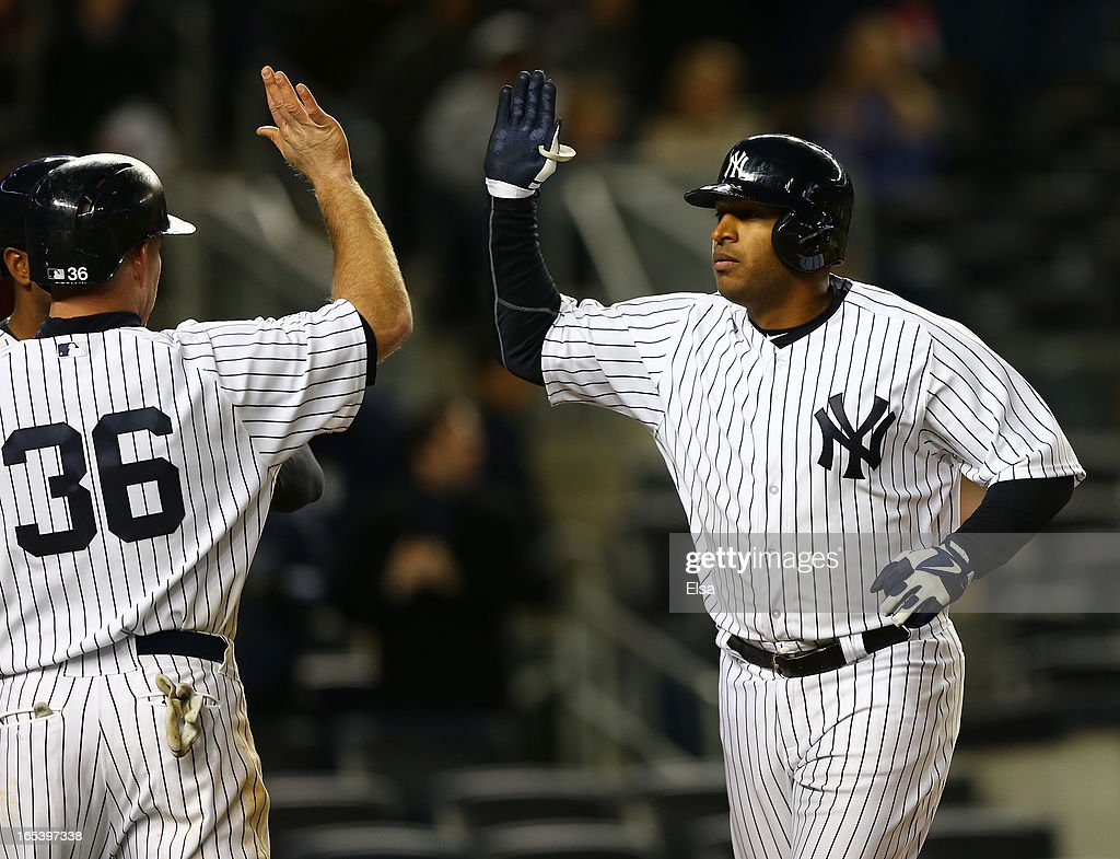 <a gi-track='captionPersonalityLinkClicked' href=/galleries/search?phrase=Vernon+Wells&family=editorial&specificpeople=212943 ng-click='$event.stopPropagation()'>Vernon Wells</a> #12 of the New York Yankees celebrates his three run homer with teammate <a gi-track='captionPersonalityLinkClicked' href=/galleries/search?phrase=Kevin+Youkilis&family=editorial&specificpeople=206888 ng-click='$event.stopPropagation()'>Kevin Youkilis</a> #26 in the eighth inning against the Boston Red Sox on April 3, 2013 at Yankee Stadium in the Bronx borough of New York City.