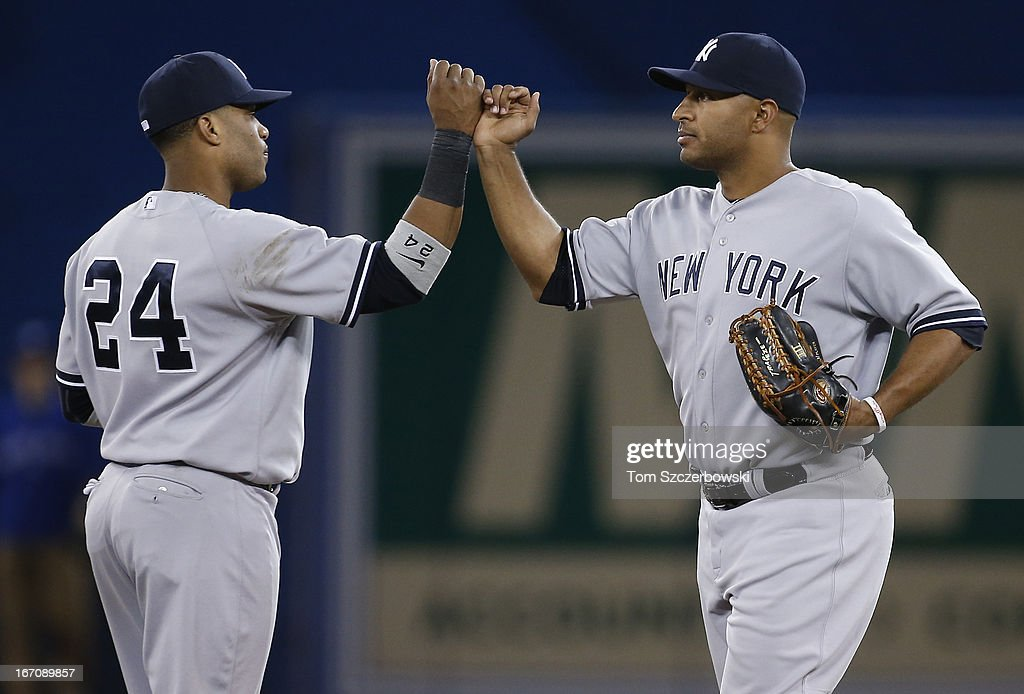 <a gi-track='captionPersonalityLinkClicked' href=/galleries/search?phrase=Vernon+Wells&family=editorial&specificpeople=212943 ng-click='$event.stopPropagation()'>Vernon Wells</a> #12 of the New York Yankees celebrates their victory with <a gi-track='captionPersonalityLinkClicked' href=/galleries/search?phrase=Robinson+Cano&family=editorial&specificpeople=538362 ng-click='$event.stopPropagation()'>Robinson Cano</a> #24 during MLB game action against the Toronto Blue Jays on April 19, 2013 at Rogers Centre in Toronto, Ontario, Canada.