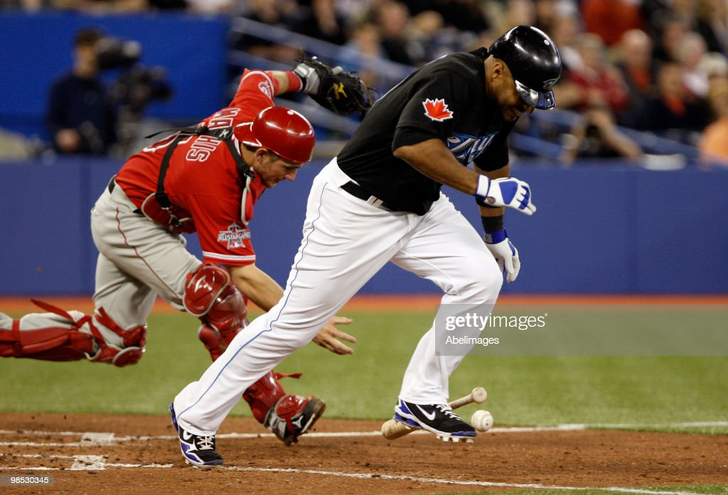 Vernon Wells of the Toronto Blue Jays scrambles to first while Jeff Mathis of the Los Angeles Angels of Anaheim grabs the ball during a MLB game at...