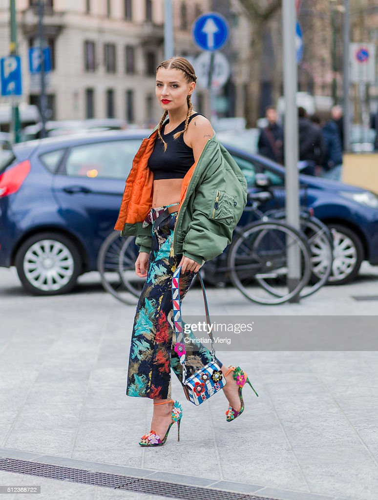 Veronica Ferraro wearing a colorful printed pants a cropped black top and a green bomber jacket seen outside Costume National during Milan Fashion...