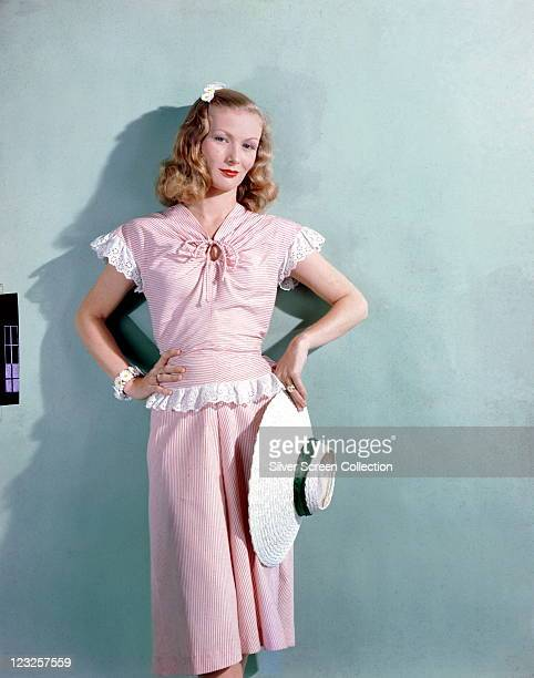 Veronica Lake US actress wearing a pink gingham dress with white lace trim holding a white widebrimmed straw hat with a green band in a studio...